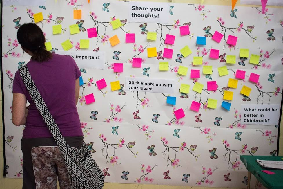 Photo of woman with dark hair, looking at a wall covered with post-it notes of ideas for the community